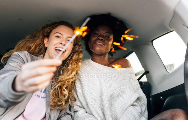 Female friends holding sparklers — Stock Photo
