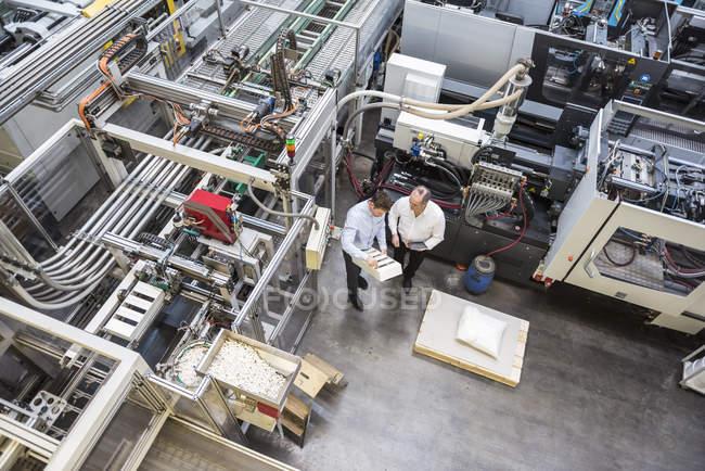 Чоловіки, вивчаючи продукт заводі — стокове фото