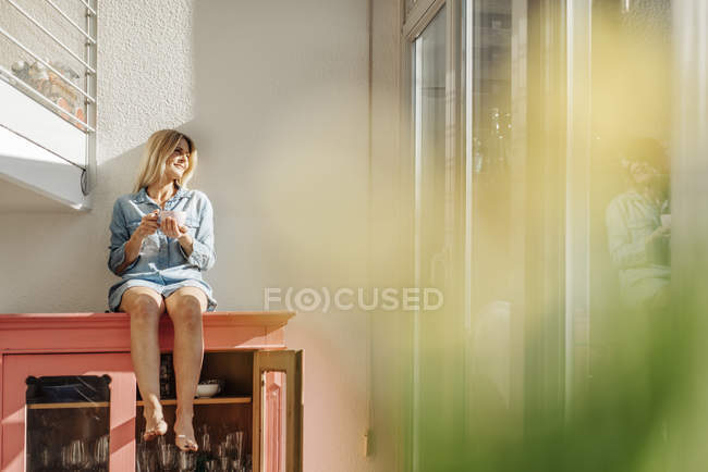 Woman sitting on cupboard with cup of coffee — Stock Photo