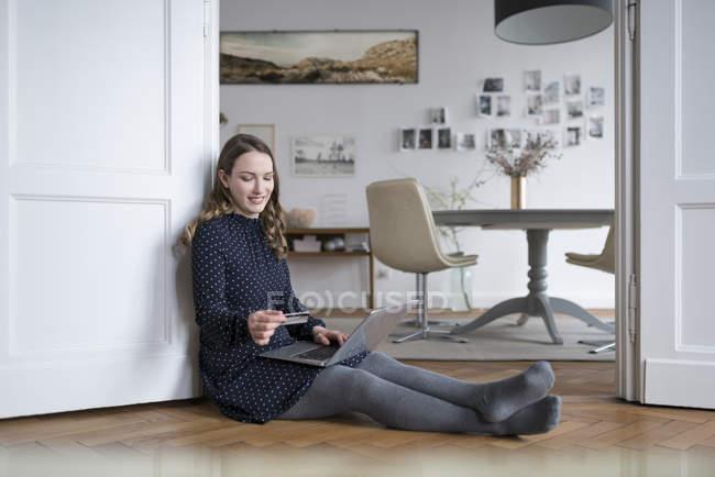 Frau mit Laptop sitzen und halten Kreditkarte — Stockfoto