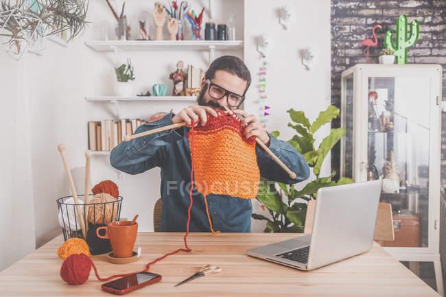 Man knitting watching tutorial on laptop — Stock Photo