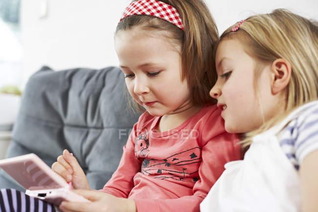 Duas meninas sentada no sofá — Fotografia de Stock