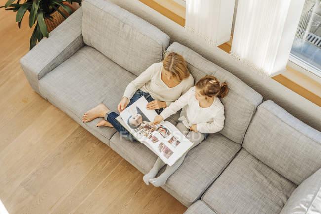 Woman and girl watching photo album — Stock Photo