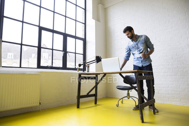 Man with coffee using laptop — Stock Photo
