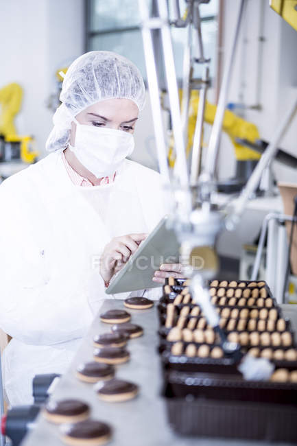 Woman in factory using tablet with robot handling cookies — Stock Photo