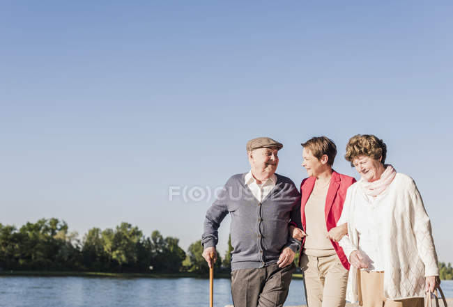 Parents strolling with adult daughter at riverside — Stock Photo