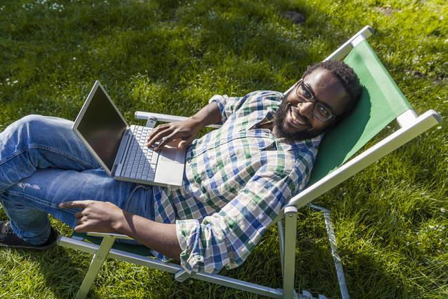 Человек с ноутбуком, сидящий на шезлонге — стоковое фото