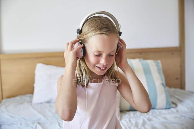 Mädchen hört Musik mit Kopfhörern zu Hause — Stockfoto