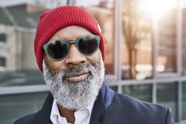 Businessman wearing red cap and sunglasses — Stock Photo