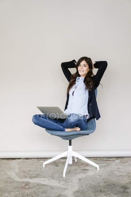 Бизнесвумен сидит на стуле с ноутбуком — стоковое фото