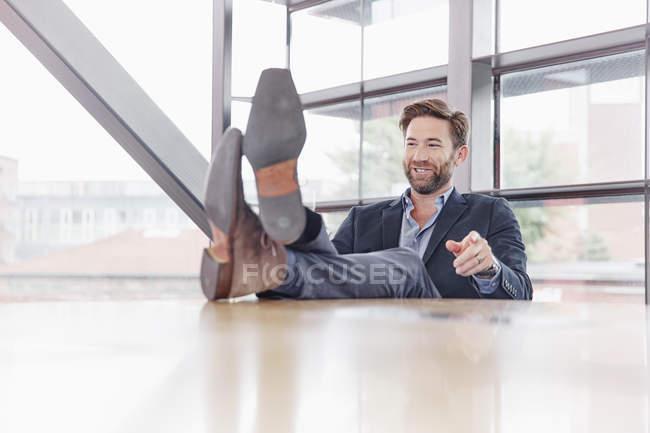 Uomo d'affari mettendo i piedi sul tavolo — Foto stock