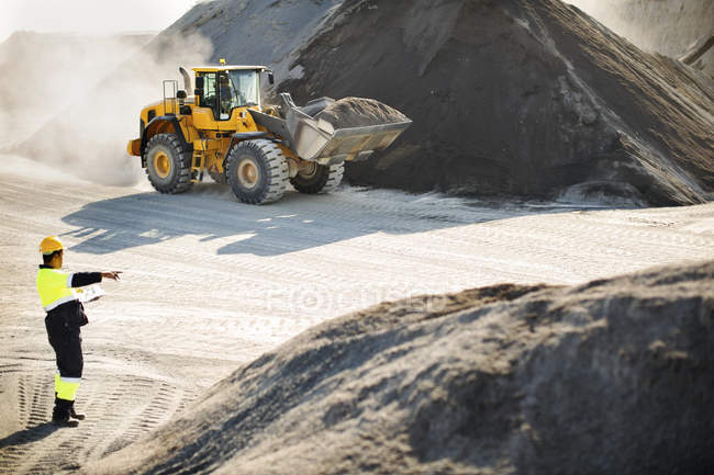 Travailleur montrant la direction à suivre pour creuser — Photo de stock