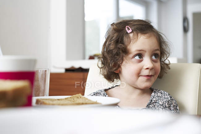 Smiling little girl at table — Stock Photo