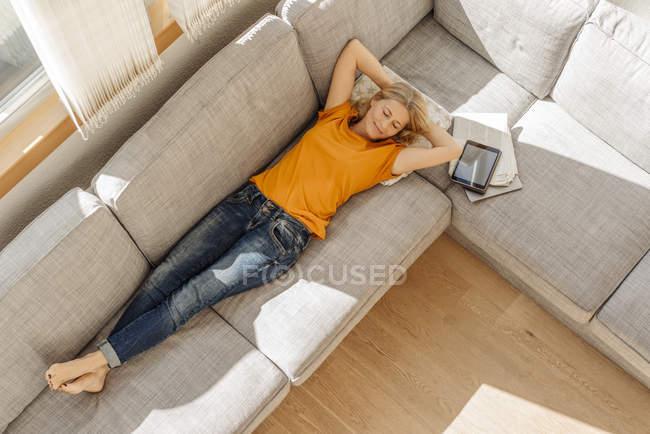 Femme couchée sur le canapé — Photo de stock