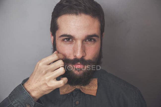 Bearded man adjusting moustache — Stock Photo