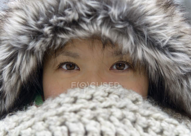 Portrait of woman wearing fur cap covering nose and mouth with scarf — Stock Photo