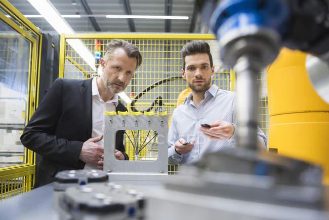 Hommes d'affaires en observant le robot industriel — Photo de stock