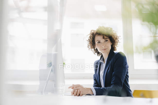 Businesswoman sitting at desk — Stock Photo