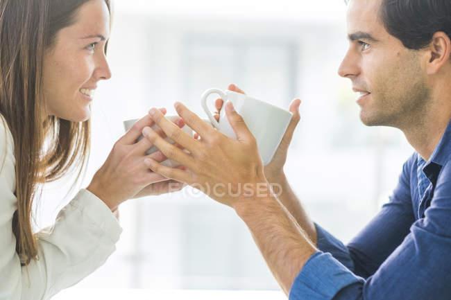 Pareja de enamorados con tazas de café - foto de stock