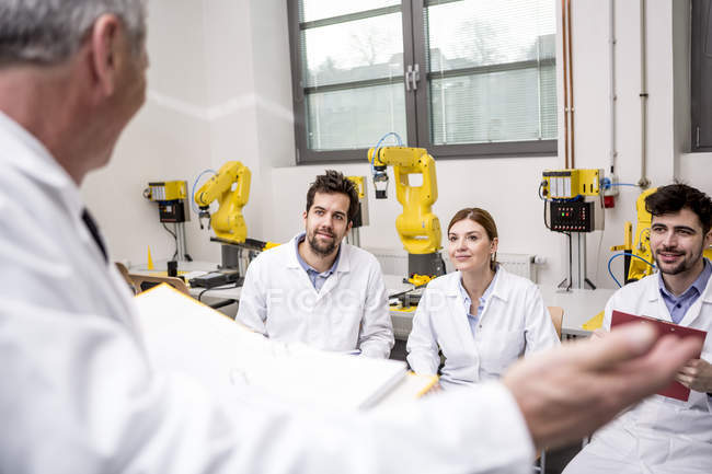 Engineers looking at boss making a speech — Stock Photo