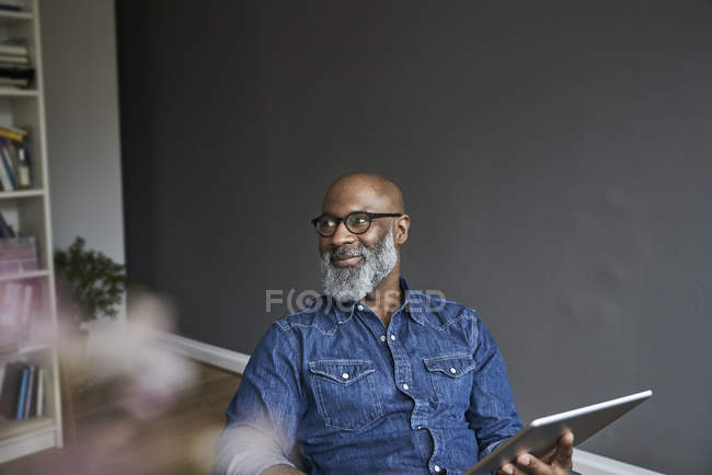 Smiling mature man holding tablet — Stock Photo