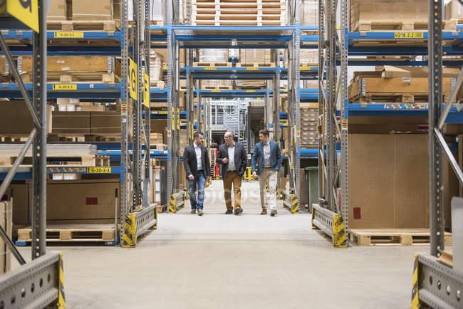 Hommes marchant dans l'entrepôt d'usine — Photo de stock