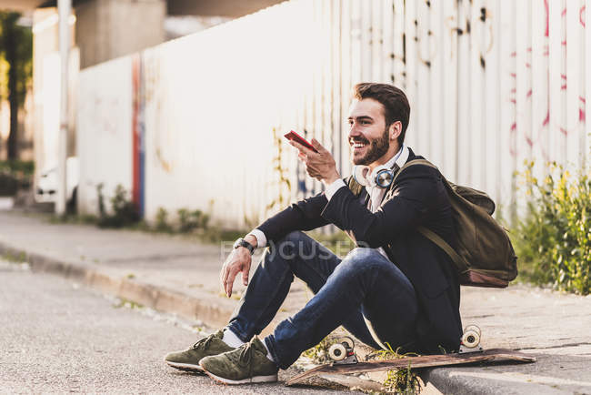 Man sitting on pavement using cell phone — Stock Photo