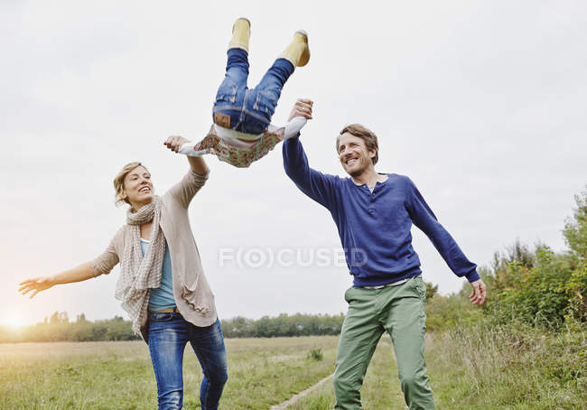 Family lifting up daughter — Stock Photo