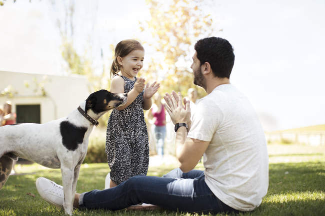 Feliz padre, hija y perro en el jardín - foto de stock