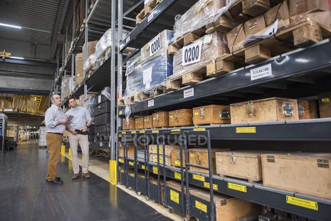 Hommes examinant entrepôt usine — Photo de stock