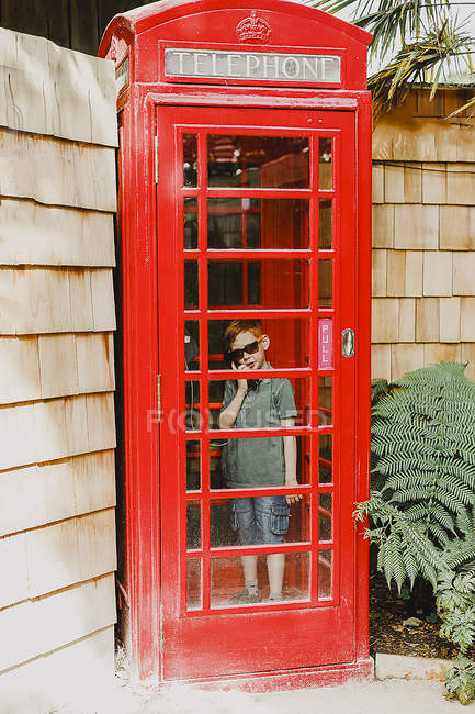 Boy in red phone box — Stock Photo