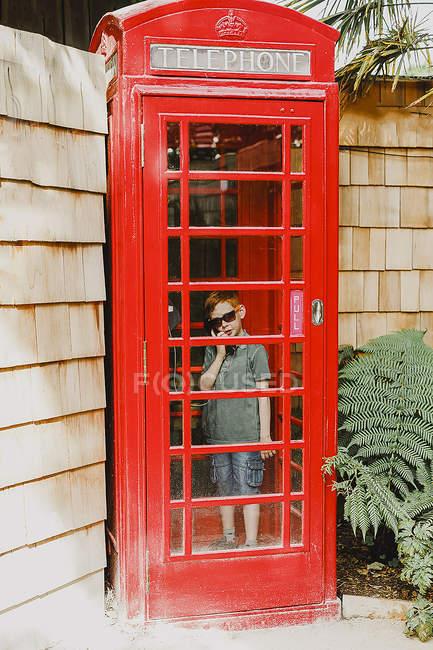Хлопчик у вікні червоний телефон — стокове фото