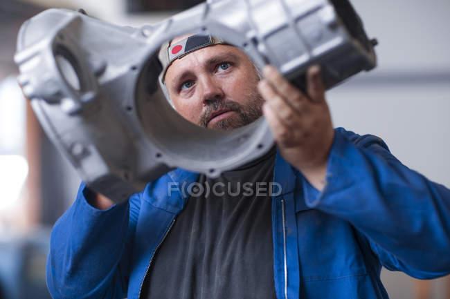 Mechanic holding car transmission — Stock Photo