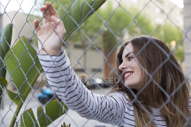 Молодая женщина за проволочным забором — стоковое фото