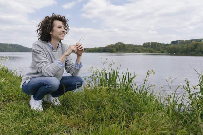 Mulher agachada na margem do lago — Fotografia de Stock