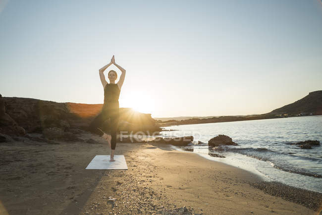 Greece, Crete, woman practicing yoga on the beach at sunset — Stock Photo