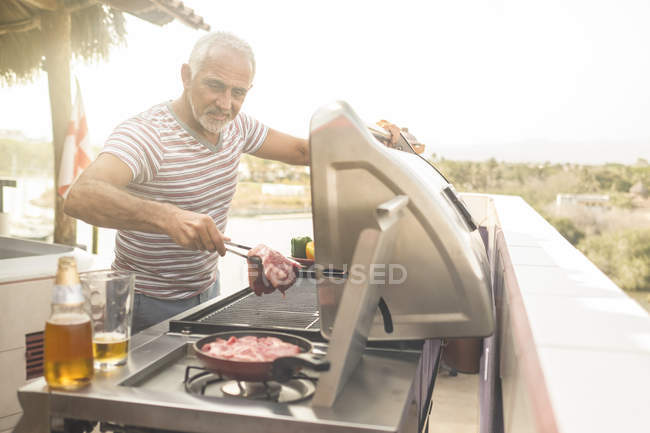 Mature man grilling steaks on a gas grill on his penthouse terrace — Stock Photo