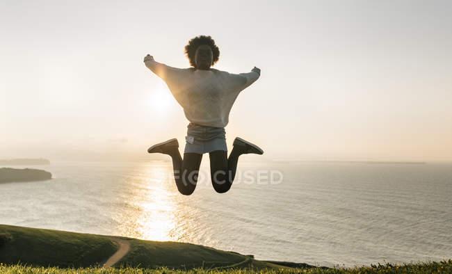 Young woman jumping at coast — Stock Photo