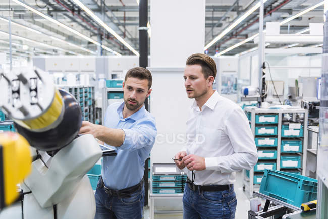 Men examining assembly robot — Stock Photo