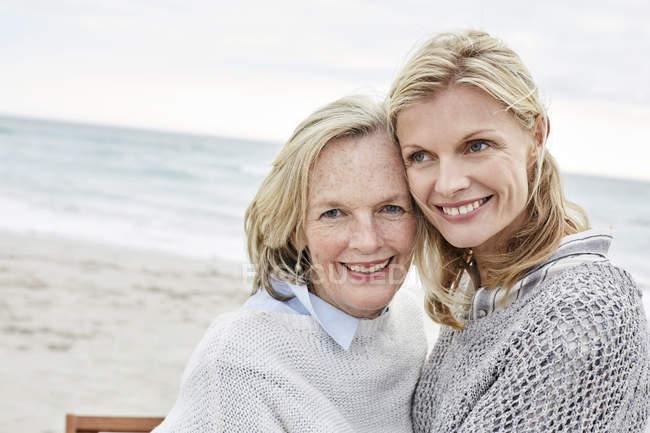 Madre e hija abrazándose en la playa - foto de stock