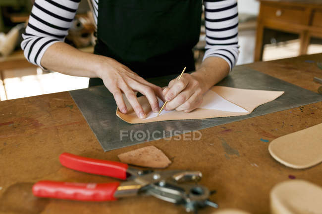 Cropped view of shoemaker working on template in workshop — Stock Photo
