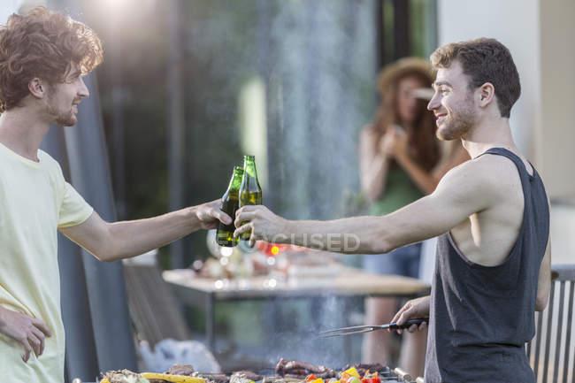 Two men clinking beer bottles — Stock Photo