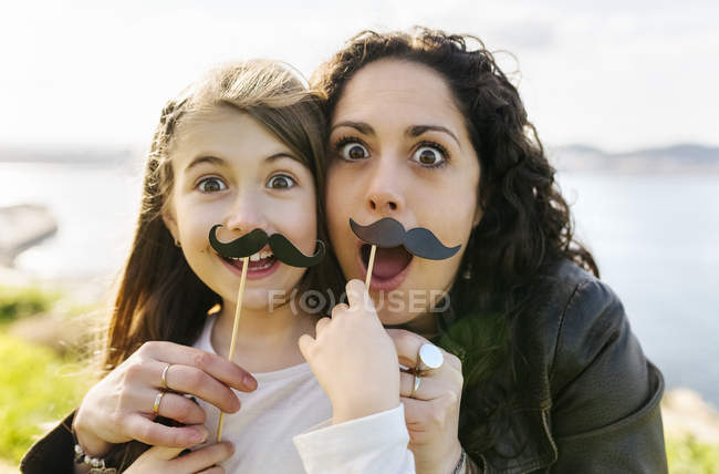 Mother and daughter holding fake moustaches — Stock Photo