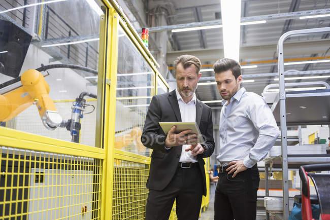 Бизнесмены наблюдают за промышленным роботом — стоковое фото
