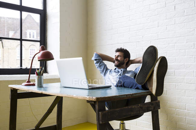 Man sitting with feet up at desk — Stock Photo