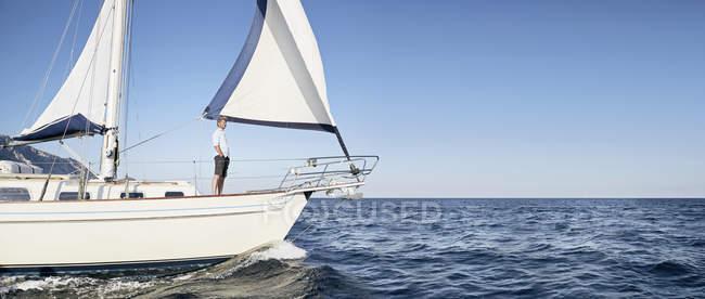 Зрелый человек, стоящий на парусной лодке — стоковое фото