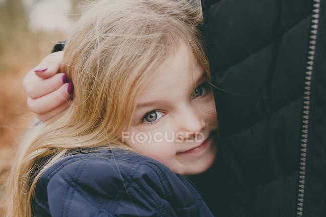 Girl cuddling  mother — Stock Photo