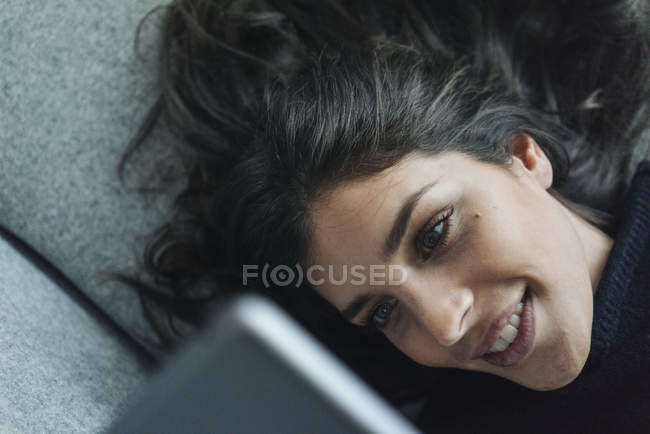 Woman lying on couch and using tablet — Stock Photo