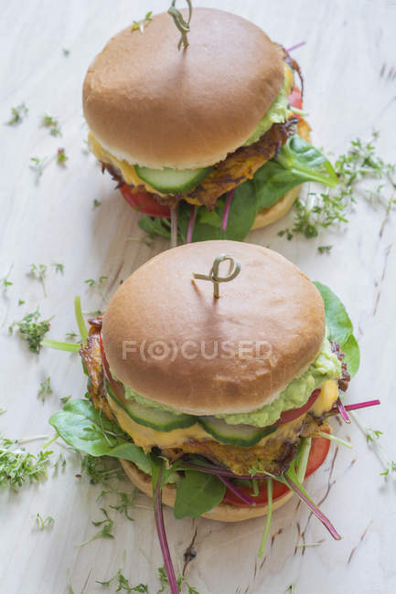 Two veggie burgers with sweet potato patties, avocado dip, cheese and vegetables — Stock Photo