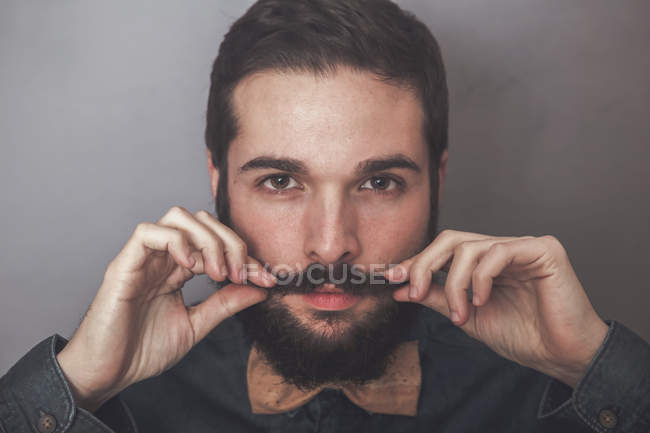 Bearded man adjusting mustaches — Stock Photo